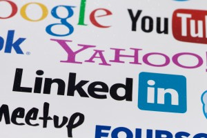 Collection of inscriptions, symbols of popular social media: Youhoo, Google, Linkedin, Facebook, YouTube and others printed on paper. Selective focus